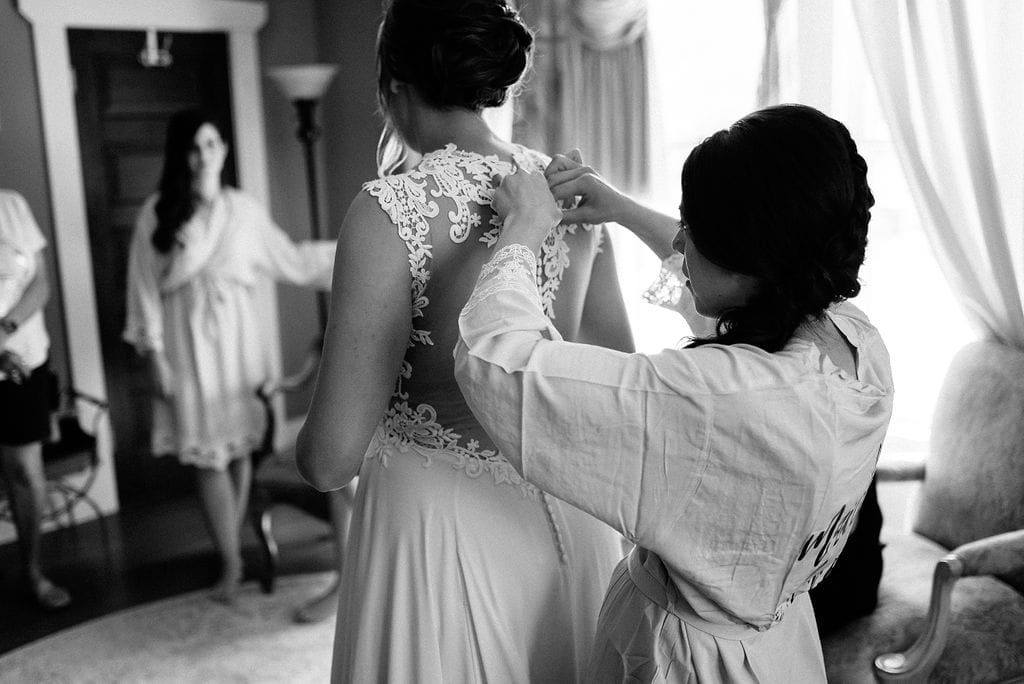 Bride and Bridesmaid getting dress on