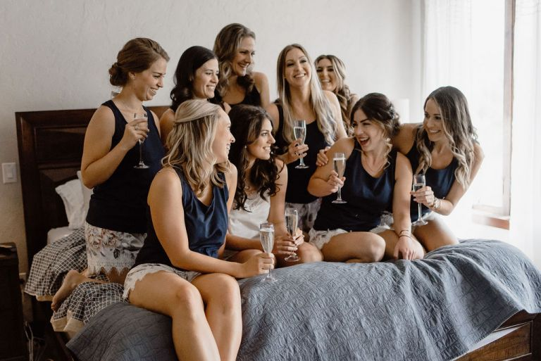 Bride and Bridesmaids Toasting on Bed in Pajamas
