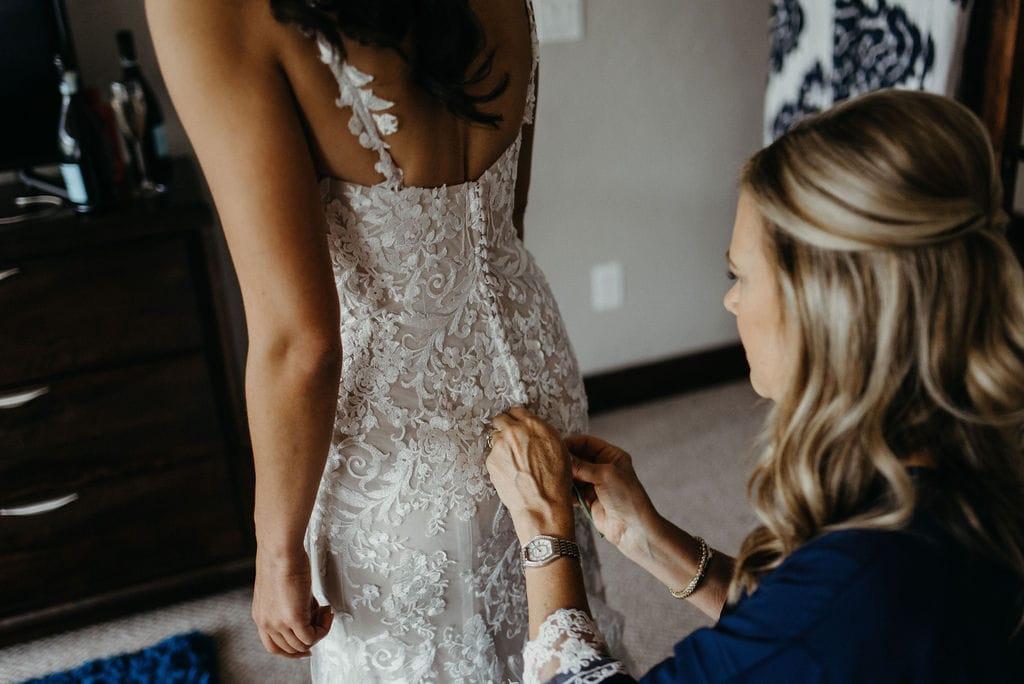 Bride getting dress on in Winter Park, Colorado