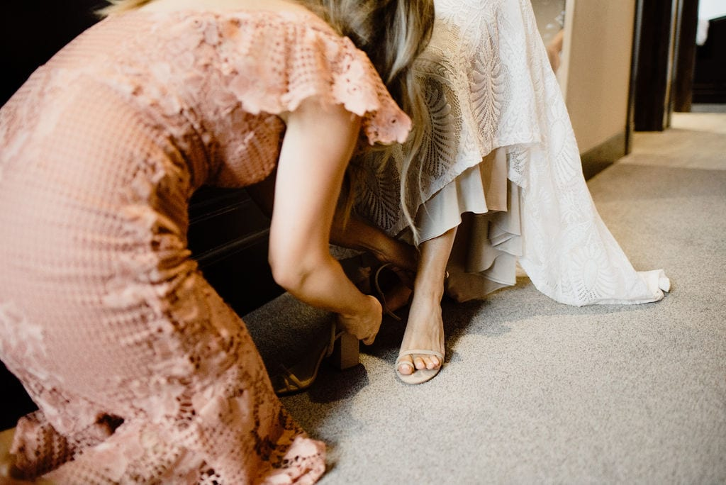 Putting shoes on the bride
