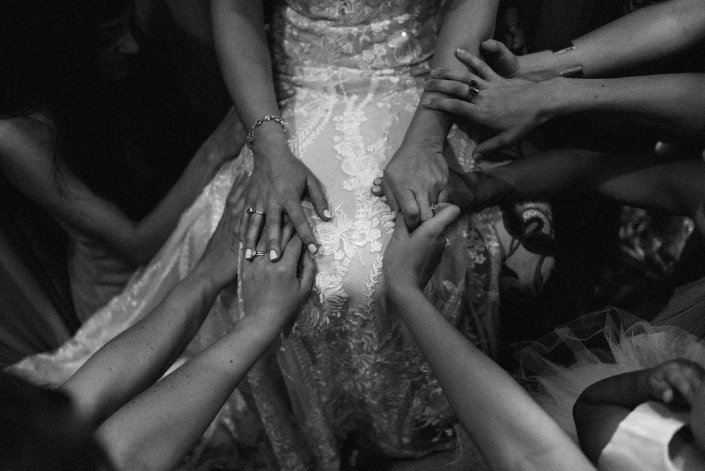 Hands on bride for prayer