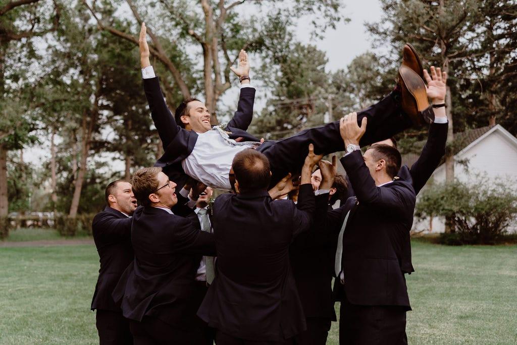 Groomsmen holding up groom