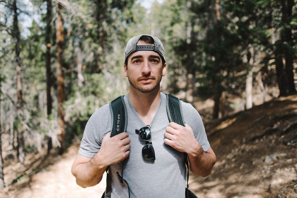 Close up of hiker on hiking trail with backwards hat and sunglasses on shirt