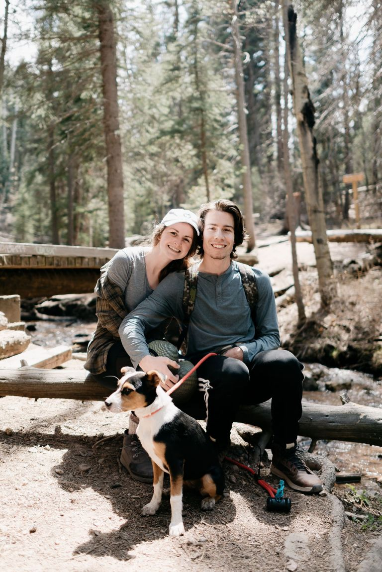 cute couple and their puppy on a hiking trail in evergreen