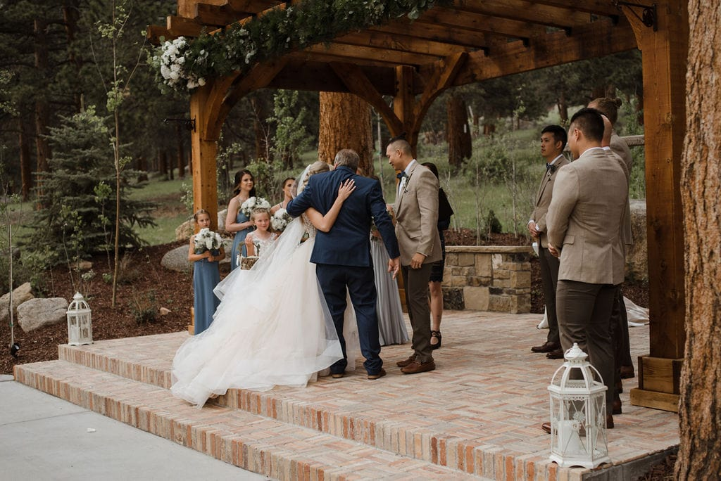 Bride walking down aisle with her dad At Della Terra in Estes Park, Colorado