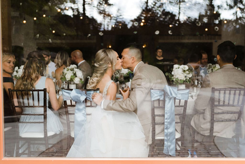 Bride and Groom Kiss during wedding reception as seen through the window of the venue