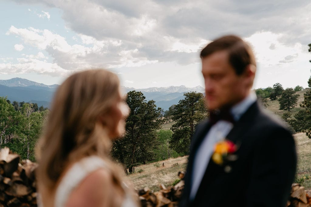 Artsy photo of bride and groom with mountains in the background