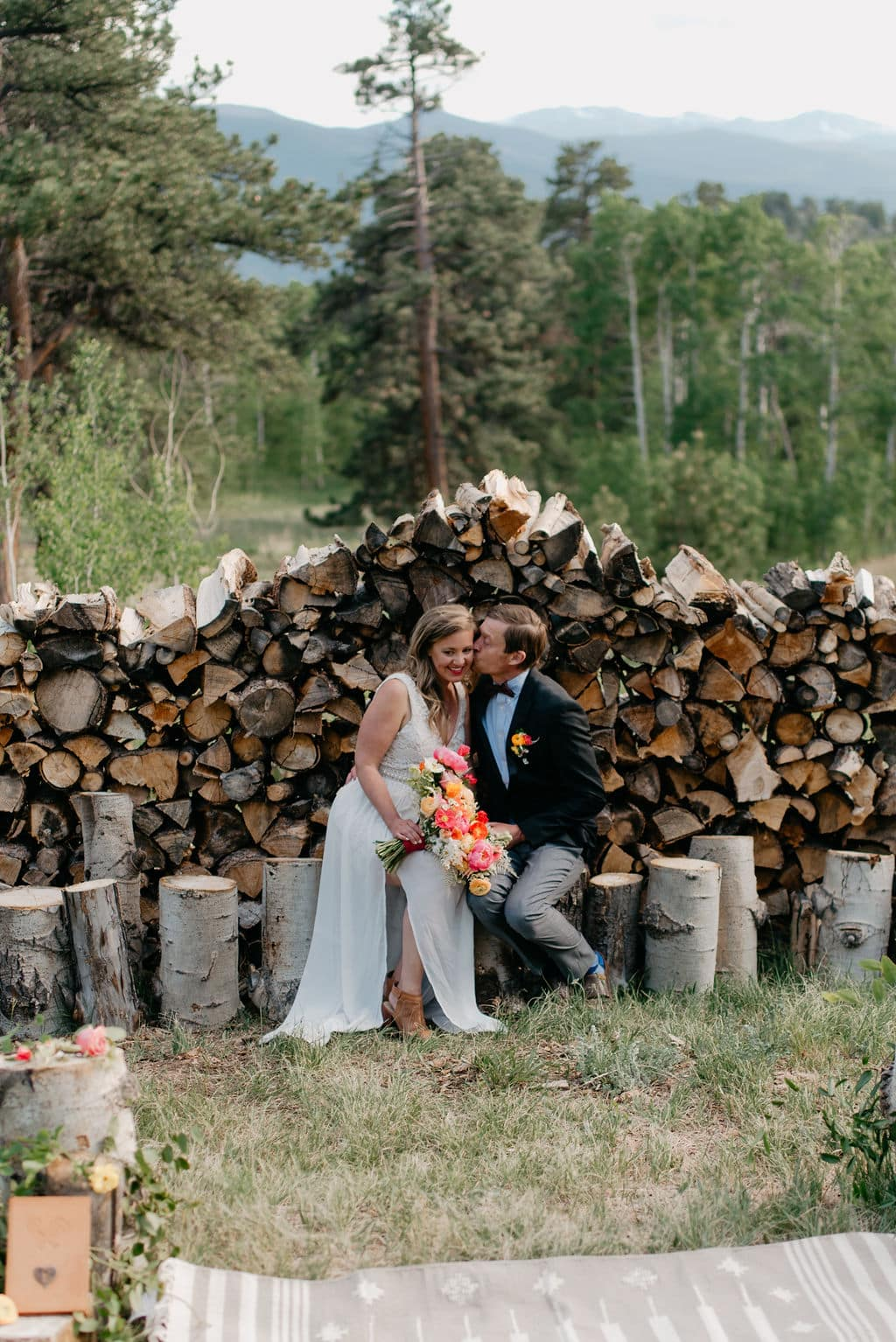 Romantic bride and groom portraits with firewood pile at new colorado elopement location