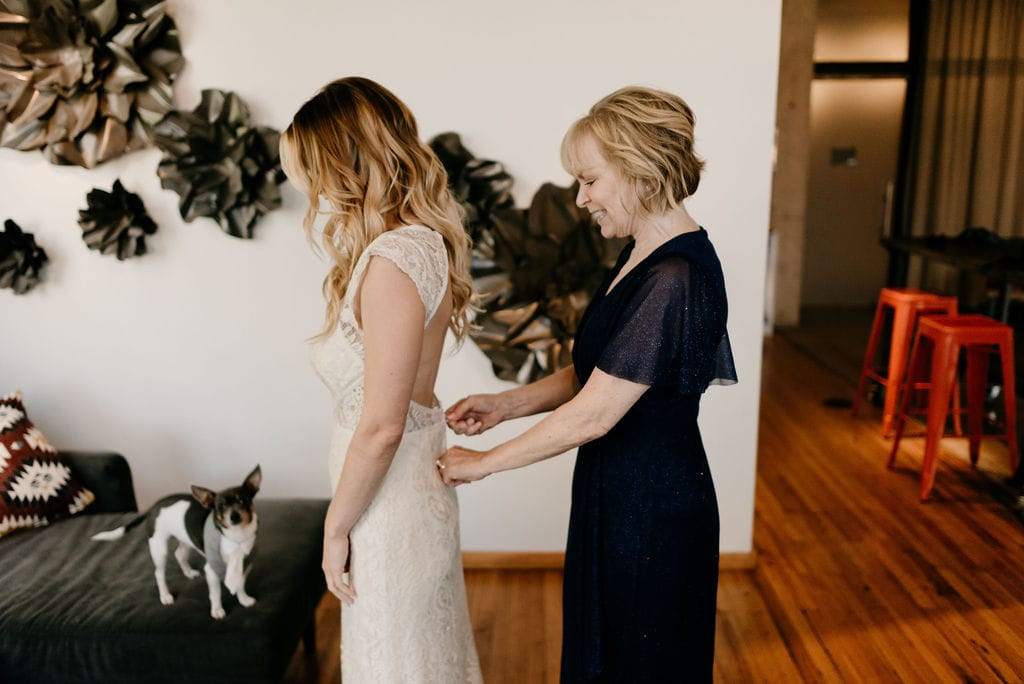 Bride getting dress on at dallas wedding at hickory street annex