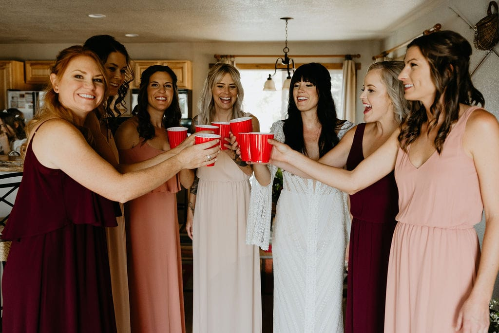 Bride taking shots with her bridesmaids after getting ready