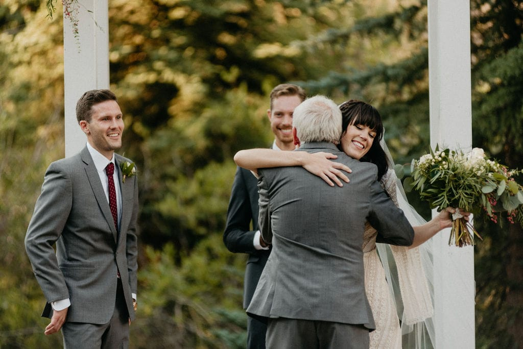 Bride gives her dad a hug at her wedding ceremony in colorado