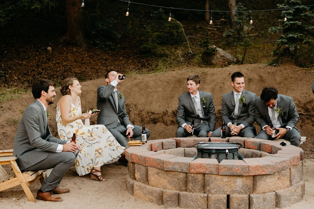 wedding guests hang out around fire pit