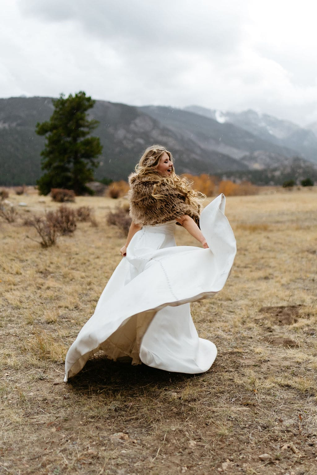 Bride dances in the rain around amongst mountains in rocky mountain national park