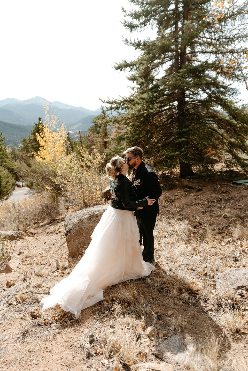 Bride and groom kiss before their estes park elopement