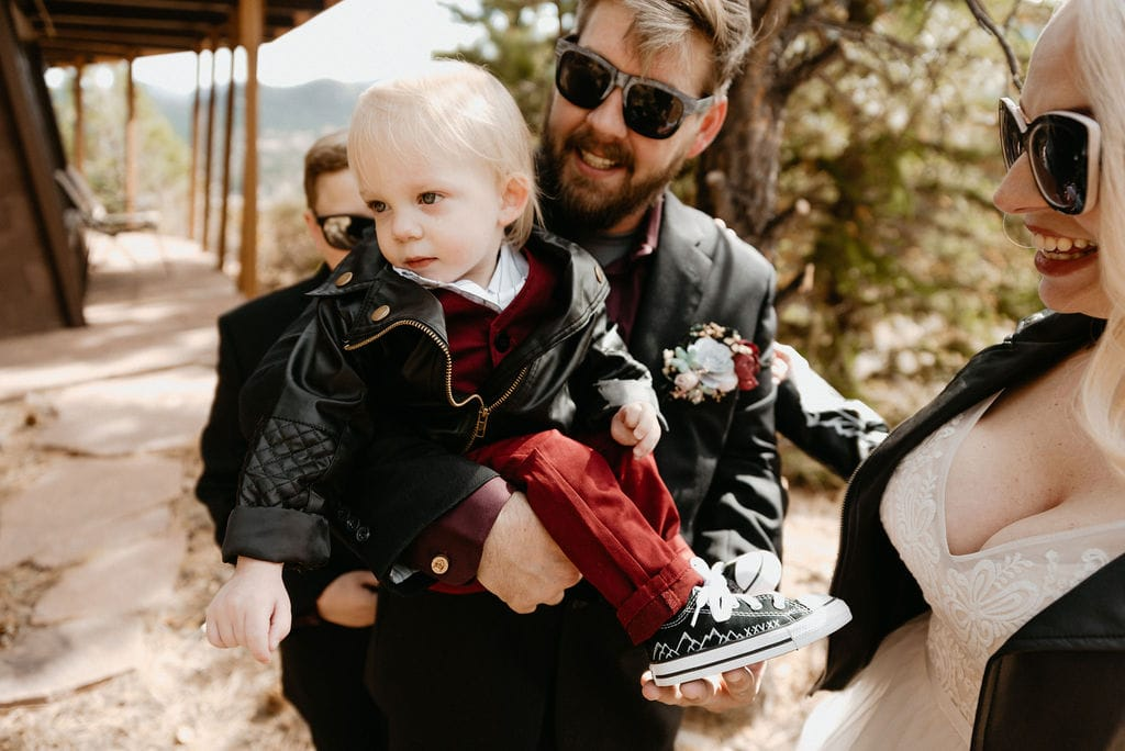 Bride and groom hang out and show off babys custom converse before their estes park elopement