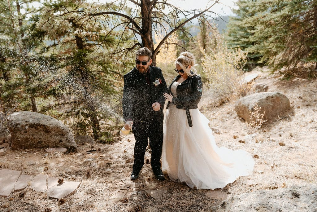 Bride and groom pop champagne bottle to celebrate them getting married in hermit Park