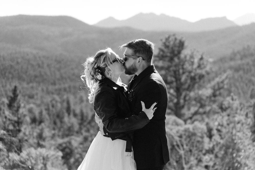 Bride and grooms first kiss at their estes park elopement in hermit park