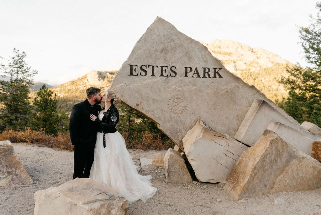 Bride and groom pose after their hermit park elopement at the estes park sign